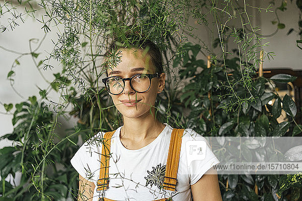 Portrait of a young woman surrounded by plants