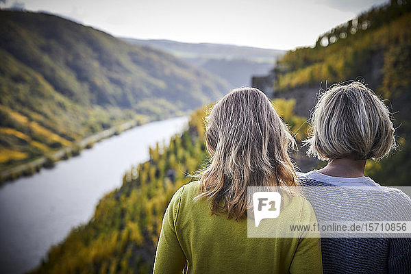Two mature women enjoying the view from a mountain