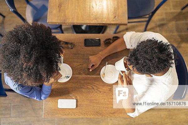 Schülerinnen und Schüler beim Kaffeetrinken in einem Café  von oben Schülerinnen und Schüler beim Kaffeetrinken in einem Café, von oben
