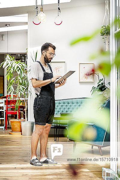 Junger Mann in Latzhose steht in seinem Wohnzimmer und benutzt digitales Tablett