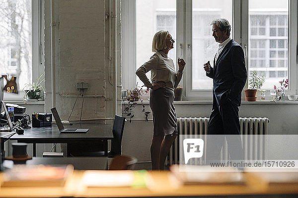 Businessman and businesswoman talking at the window in office
