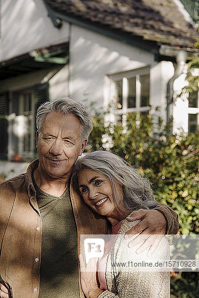 Portrait of senior couple in garden of their home