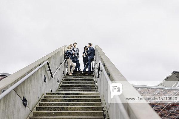 Geschäftsleute  die auf einer Außentreppe stehen