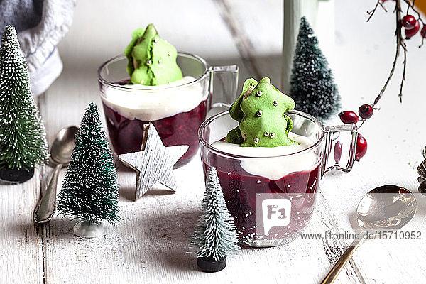 Tassen mit rotem Brei und grünen Makronen-Weihnachtsbäumen