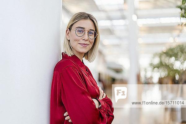 Porträt einer selbstbewussten jungen Geschäftsfrau  die sich an eine Säule lehnt