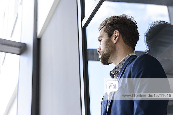 Young businessman leaning against the window