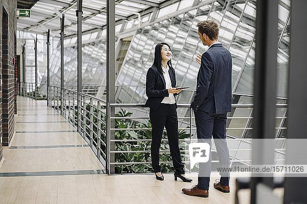 Geschäftsmann und Geschäftsfrau mit Tablett sprechend in modernem Bürogebäude