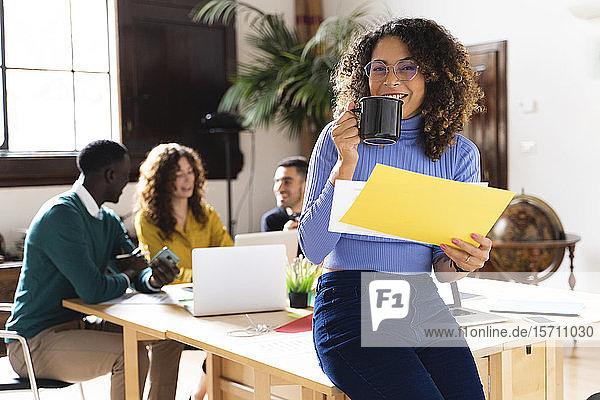 Porträt einer lächelnden Frau im Büro mit Kollegen im Hintergrund