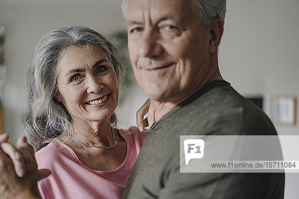 Portrait of happy senior couple dancing at home
