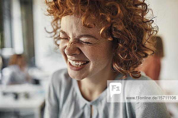 Porträt einer lachenden Geschäftsfrau mit geschlossenen Augen im Amt