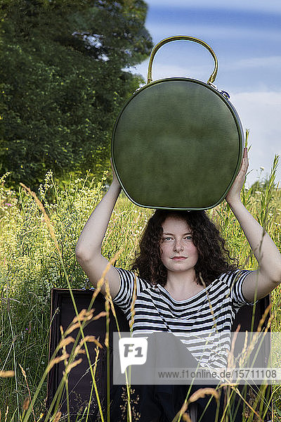 Portrait of young woman sitting in suitcase on a meadow with hatbox on top of her head