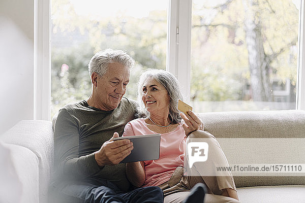 Happy senior couple relaxing on couch at home using tablet for online shopping