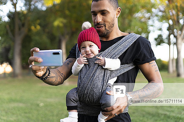 Young father carrying baby son in a baby sling  taking smartphone selfie