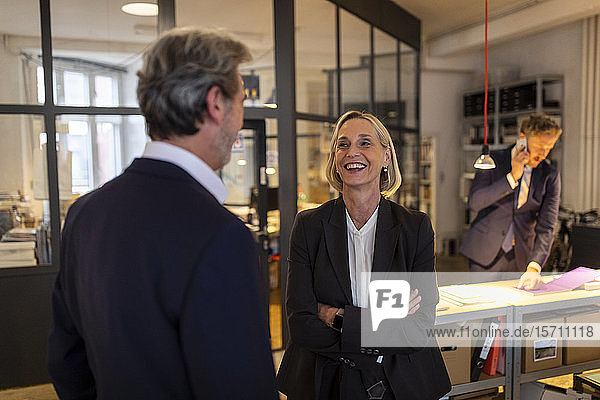 Smiling businesswoman and businessman talking in office