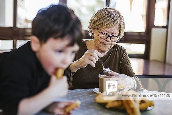Großmutter und Enkel frühstücken gemeinsam zu Hause am Tisch