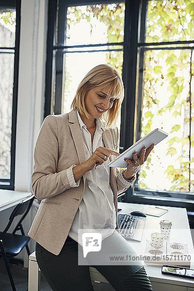 Schwangere Geschäftsfrau benutzt Tablett im Büro