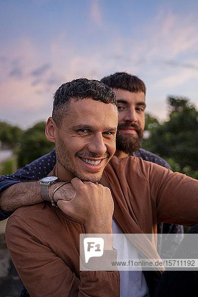 Porträt eines glücklichen schwulen Paares im Freien bei Sonnenuntergang