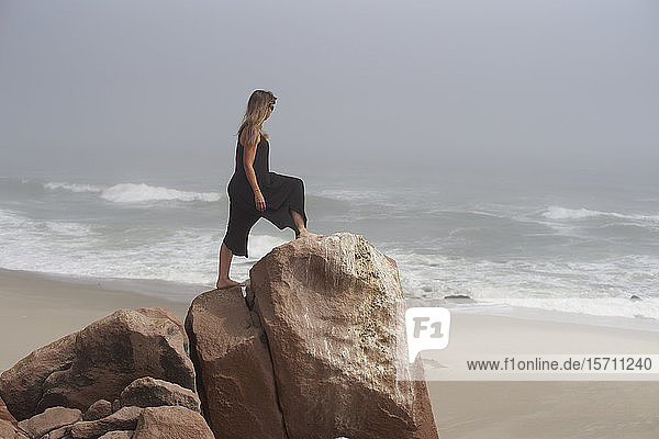 Woman standing on a rock looking to the ocean  Cape Cross  Namibia