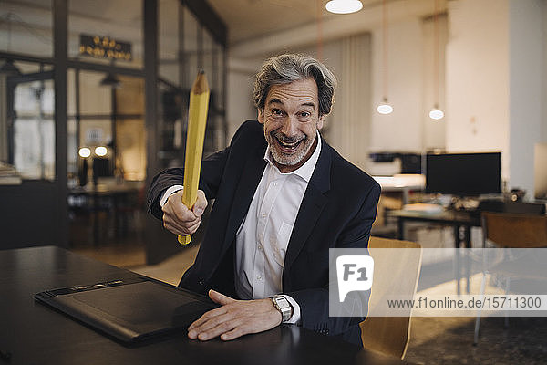 Silly senior businessman with giant pencil at desk in office