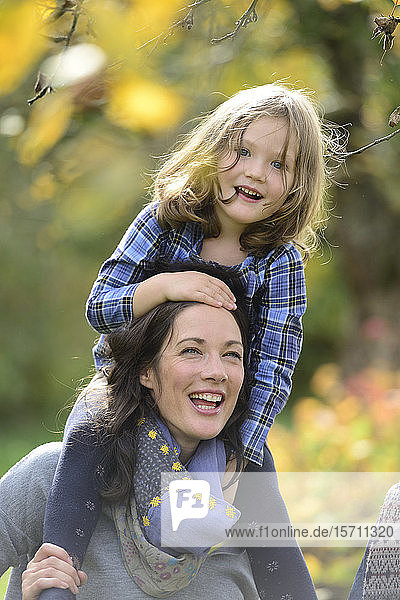 Daughter sitting on shoulders of her mother and laughing