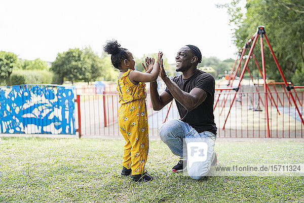 Glückliche Vater und Tochter beim Klatschspiel in einem Park