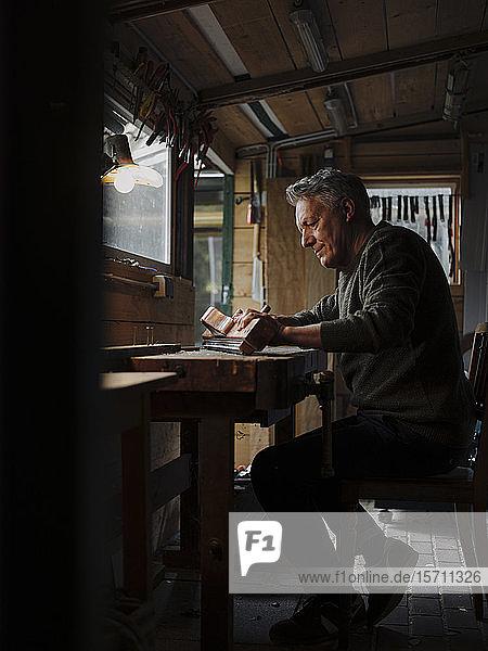 Älterer Mann arbeitet in der Werkstatt an einem Stück Holz