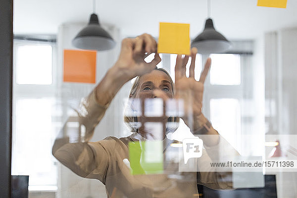 Mature businesswoman with adhesive notes on glass pane in office