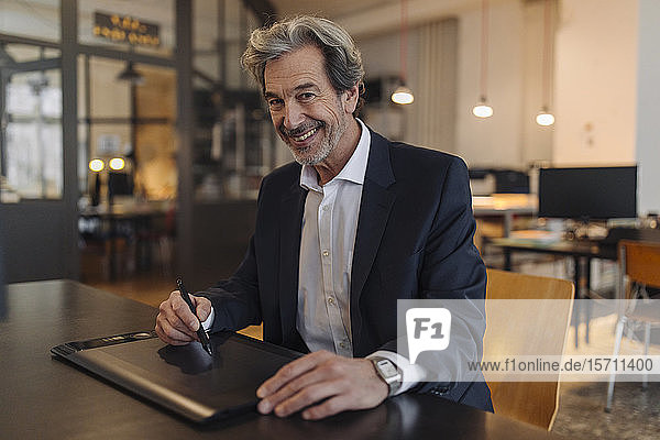Portrait of smiling senior businessman using graphics tablet at desk in office