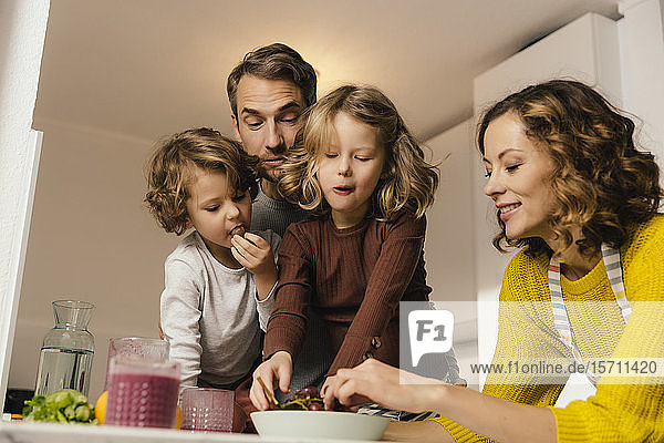 Family eating grapes in kitchen