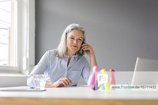 Reife Geschäftsfrau am Telefon spielt mit Stecknadeln auf dem Schreibtisch im Büro