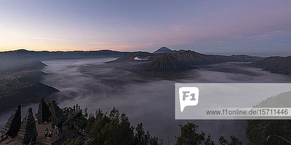 Indonesien  Ost-Java  Panorama des in dichten Nebel gehüllten Mount Bromo in der Morgendämmerung