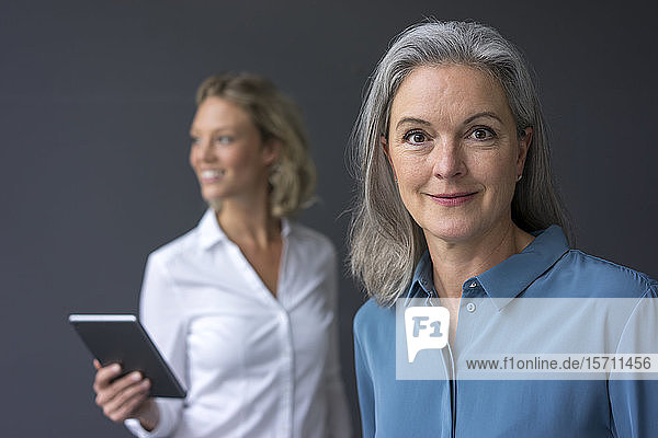 Porträt einer selbstbewussten reifen Geschäftsfrau mit einer jungen Geschäftsfrau im Hintergrund