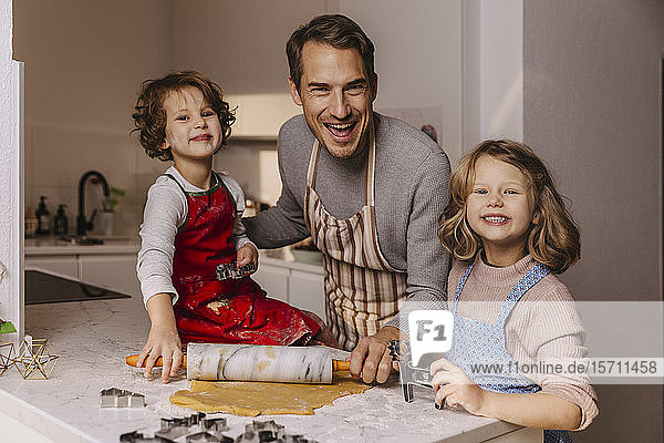 Happy father with two daughters preparing Christmas cookies in kitchen