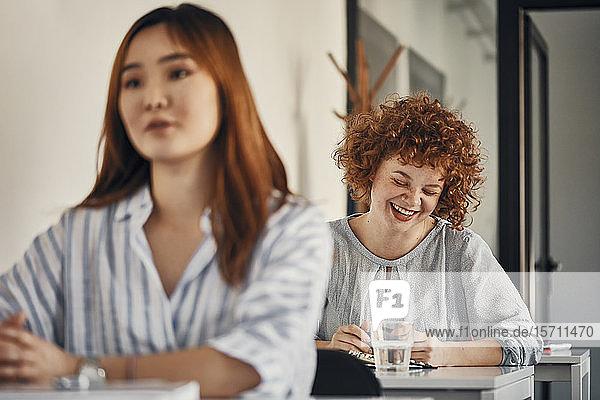 Happy businesswoman sitting at desk in a workshop