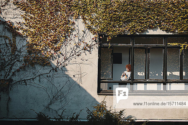 Geschäftsfrau  die mit einem Smartphone am Fenster eines Bürogebäudes steht