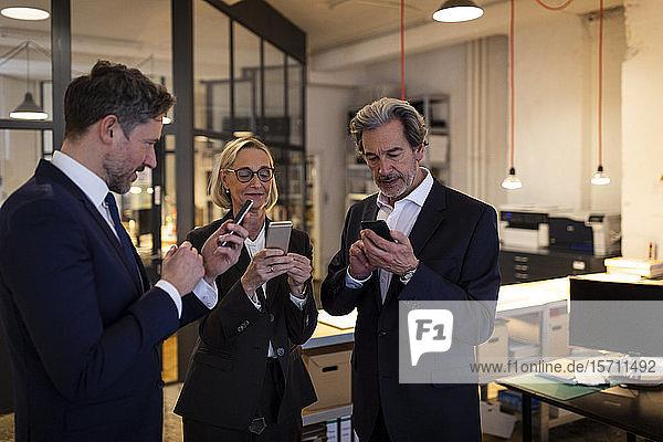 Geschäftsleute  die im Büro Smartphones benutzen