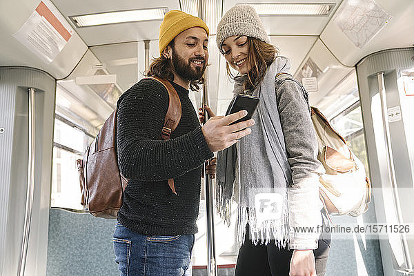 Young couple using smartphone on a subway