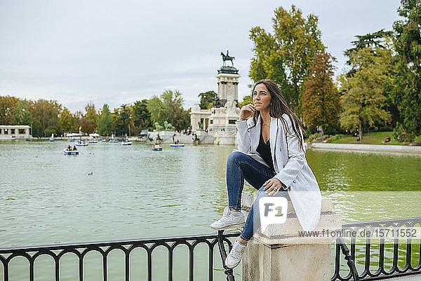 Nachdenkliche Frau sitzt an einem See im Park El Retiro  Madrid  Spanien