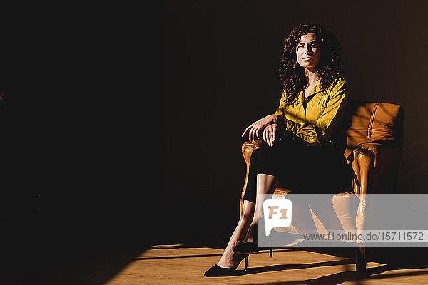 Porträt einer ernsten Frau im Ledersessel sitzend
