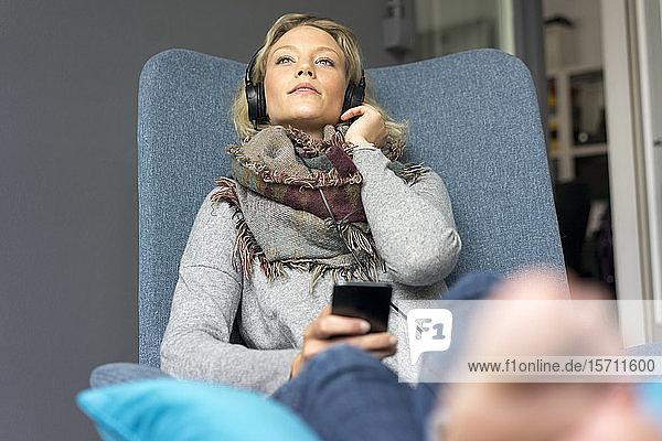 Junge Frau sitzt im Sessel und hört Musik mit Kopfhörern
