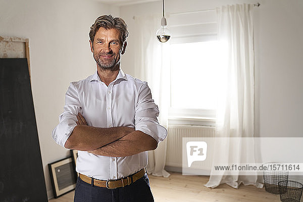 Portrait of smiling mature man at home