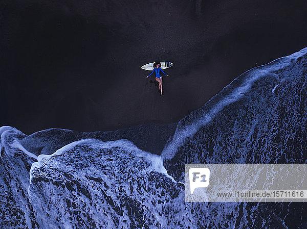 Luftaufnahme einer jungen Frau mit Surfbrett am Strand  Strand von Kedungu  Bali  Indonesien