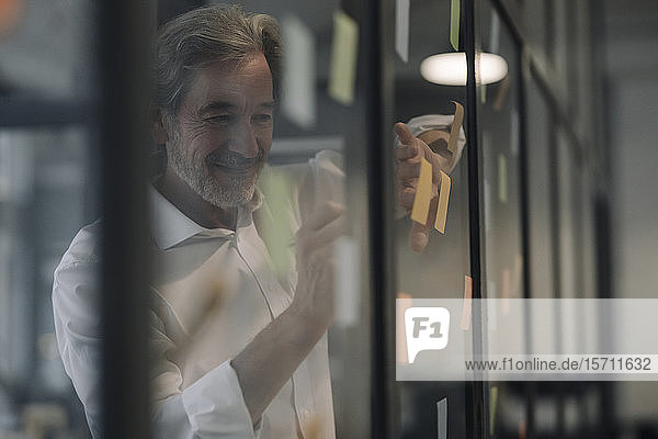 Senior businessman attaching adhesive notes at glass pane in office