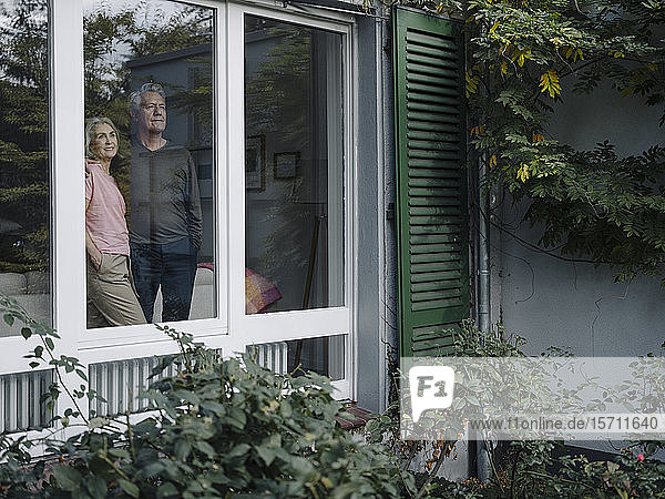 Senior couple behind windowpane of their home looking out