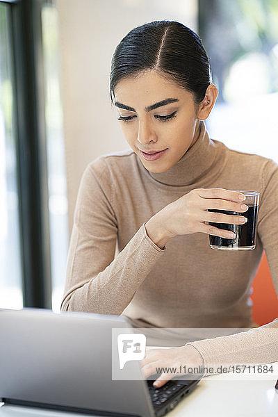 Junge Frau bei einem Drink und mit Laptop in einem Café
