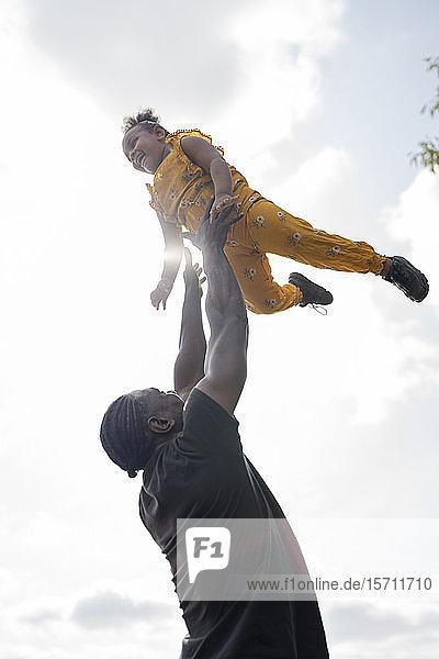 Vater wirft glückliche Tochter in die Luft