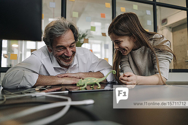 Happy senior buisinessman and girl playing with chameleon figurine in office