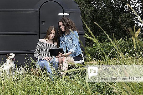 Zwei Freunde sitzen auf einer Wiese vor einem schwarzen Wohnwagen und schauen auf ein digitales Tablet