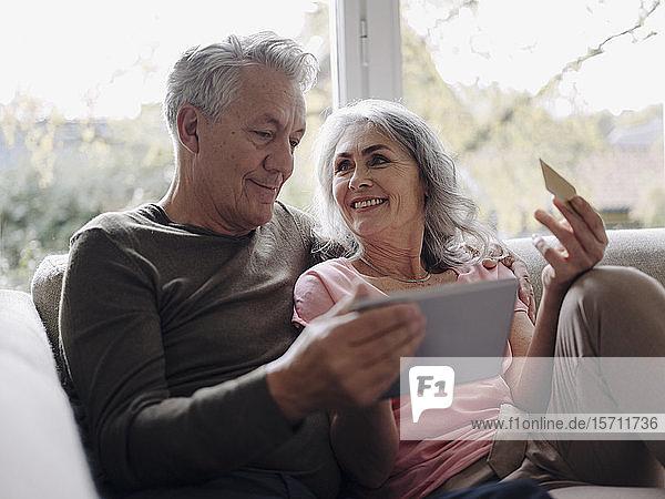 Glückliches älteres Ehepaar entspannt sich zu Hause auf der Couch und nutzt Tablet zum Online-Shopping