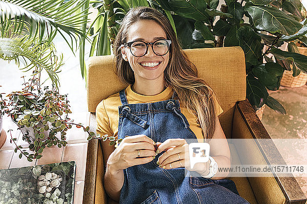 Portrait of a happy young woman sitting in armchair surrounded by plants
